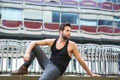 Männliches Mode-Modell, das draußen im Stadtgebiet sitzt Stockbilder
