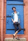 Männliches Mode-Modell mit dem Bart, der im Eingang lächelt Lizenzfreie Stockfotografie
