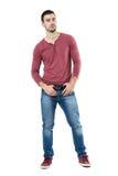 Männliches Modell der kühlen jungen Machomode, das den Gurt betrachtet Kamera aufwirft und hält Stockfoto