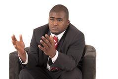 Männliches Modell im Anzug und in roter gestreifter Bindung, die im Stuhl sitzen Stockbild