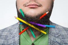 Männliches Nahaufnahmeporträt mit Bleistiften in seinem Bart Stockbild