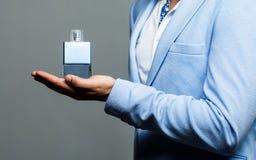 Männliches Parfüm, bärtiger Mann in einer Klage Mannparfüm, Duft Männliche Haltenflasche Parfüm Parfüm oder Cologne stockbild