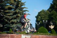 Männliches Radfahrertraining auf Straßenrand Stockfoto