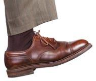 Männliches rechtes Bein im braunen Schuh unternimmt einen Schritt Stockfoto