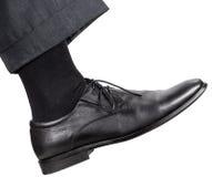 Männliches rechtes Bein im schwarzen Schuh unternimmt einen Schritt Lizenzfreies Stockfoto