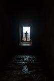 Männliches Schattenbild im leeren Innenschauen im Fenster, beleuchtet durch drastisches Sonnenlicht Stockfotos