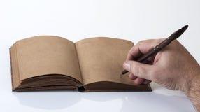Männliches Schreiben auf einem aufbereiteten Papiernotizbuch Lizenzfreies Stockbild