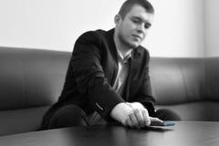 Männliches setzendes Exekutivtelefon auf der Aufenthaltsraum-Tabelle stockfotos