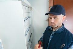 Männliches Technikerschreiben auf Klemmbrett im vorderen fusebox lizenzfreie stockbilder