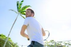 Männliches Tennisspieler-Vollendenaufschlagsspielen im Freien Stockfoto