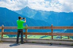 Männliches touristisches nehmendes Foto der alpinen Landschaft Lizenzfreies Stockbild