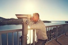 Männliches touristisches Schauen durch Teleskop Stockfoto