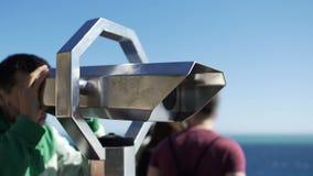 Männliches touristisches schauendes Stadtbild durch Ferngläser an der Besichtigungsplattform stock video