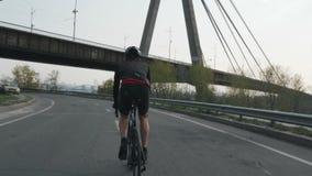 Männliches triathlete Reitenfahrrad als Teil seines Ausbildungsterminplans Er trägt schwarze Ausstattung, Sturzhelm und Sonnenbri stock video