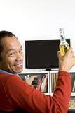Männliches trinkendes Bier des Geschäfts und überwachender Fernsehapparat Stockbilder