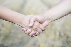 Männliches und weibliches Händchenhalten draußen über bokeh Lizenzfreies Stockfoto
