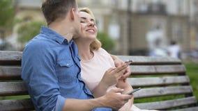 Männliches und weibliches Sitzen auf Bank mit Handys, Kerl, der Mädchen auf Backe küsst stock footage