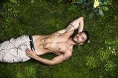 Männliches vorbildliches Entspannungslügen des hemdlosen Sitzes auf dem Gras Lizenzfreies Stockbild