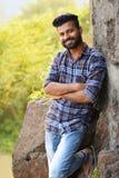 Männliches vorbildliches Lächeln an der Kamera, die auf Felsen stillsteht Mumbai stockbild