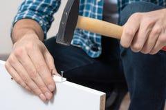Mäns att bulta för hand spikar, begreppet av möblemangenheten arkivbild