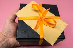 Mäns för Ribboned för handinnehavet packar in den lyxiga asken för gåvan för kuben svart, det orange bandet med överst royaltyfri bild
