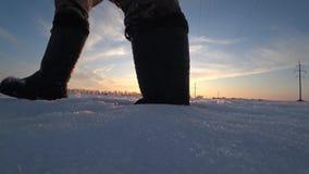Mäns fot i varma gummiarbetskängor går i djup snö på solnedgången på en solig dag för vinter stock video