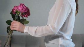 Mäns händer ger en ask med en gåva och rosor till en kvinna