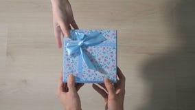 Mäns händer ger en ask med en gåva till en kvinna