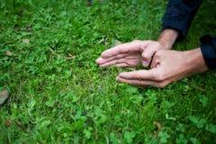 Mäns händer på gräs royaltyfri fotografi