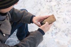Mäns händer rymmer telefonen Arkivbild