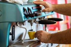 Mäns händer som gör espresso i ett kafé royaltyfri bild