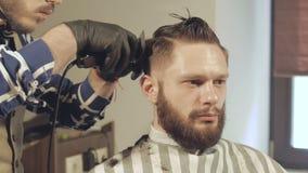 Mäns hairstyling och haircutting med hårclipperen i en barberare shoppar eller hårsalongen lager videofilmer