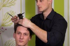 Mäns hairstyling och haircutting med hårclipperen och scissor arkivfoto