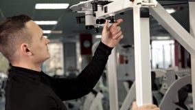 Mäns hand förminskar vikt på simulatorn, för ändringsplatta för stift vald bunt för vikt sport lager videofilmer