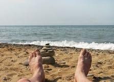 Mäns kala fot på bakgrund av havet Arkivfoton
