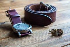 Mäns klockor och bälte och cufflincs på träbakgrund Arkivbilder