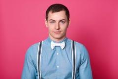 Mäns stil och modebegrepp Den stiliga blåa synade mannen med mörkt hår, slät hud, bär skjortan, bowtie, och hängslen, ser arkivbild