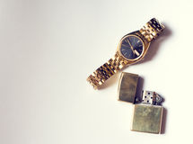 Mäns tillbehör, guld- klocka och tändare på vit Fotografering för Bildbyråer