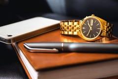Mäns tillbehör, guld- klocka, penna och mobiltelefon på läderdagboken Royaltyfri Foto
