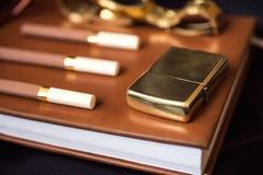 Mäns tillbehör, guld- tändare, klocka och cigaretter på läderdagboken Royaltyfri Foto
