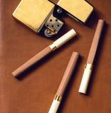 Mäns tillbehör, guld- tändare och cigaretter på Arkivfoto