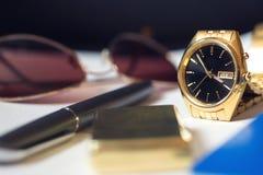 Mäns tillbehör, pass, penna, guld- klocka Arkivbild