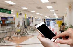 Mänsklig hållande tom skärm av smart telefon och väntande ankomster b royaltyfri bild