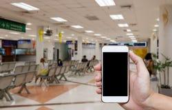 Mänsklig hållande tom skärm av smart telefon och väntande ankomster t royaltyfria bilder