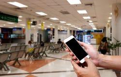 Mänsklig hållande tom skärm av smart telefon och väntande ankomster t fotografering för bildbyråer