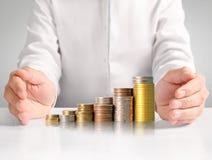 Mänsklig hand för hand som sätter myntet till pengar Royaltyfria Bilder