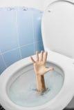 Mänsklig hand i toalettbunken eller WC som spolar och frågar för hjälp Arkivfoton
