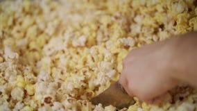 Mänsklig hand som häller klart popcorn från popcornmaskinen vid sleven lager videofilmer