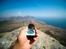 Mänsklig hand som rymmer den gamla kompasset i solig dag på suddiga berg och havet fotografering för bildbyråer