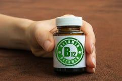 Mänsklig hand som rymmer en flaska av preventivpillerar med vitaminet B12 Arkivfoton